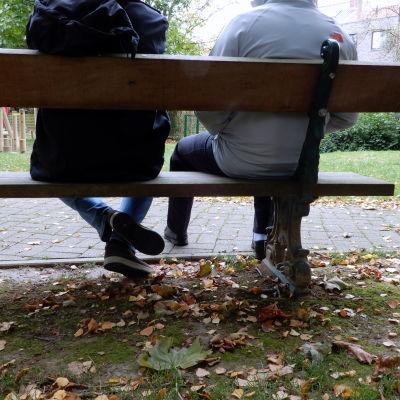 Två personer på en bänk