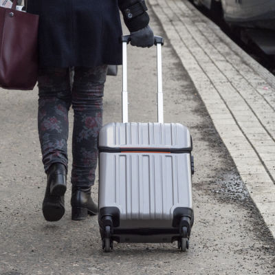 Nainen pienen matkalaukun kanssa