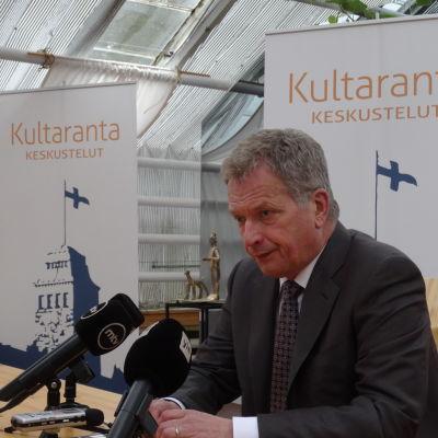 Sauli Niinistö sitter vid bord med mikrofoner på Gullrandamöte