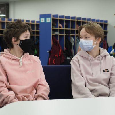 Koulupojat maskit naamallaan koulun aulassa