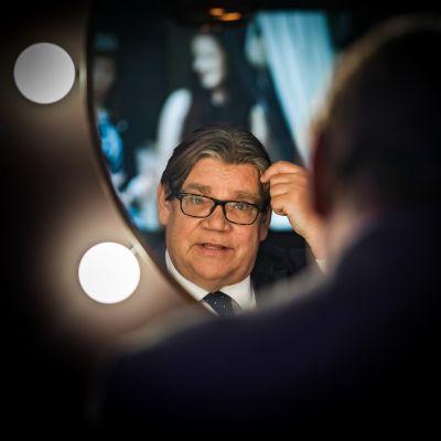 Timo Soini katselee itseään peilistä.