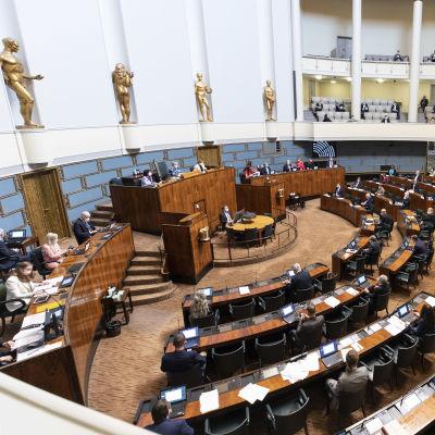 Halvfullt i riksdagens plenisal, sett från över läktaren