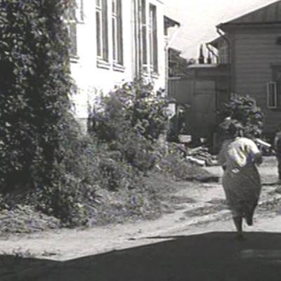 Näyttelijät juoksevat Turkulaisessa puutalomiljöössä. Kansallinen audiovisuaalinen instuutti haluaa tietää mikä on kuvauspaikka.