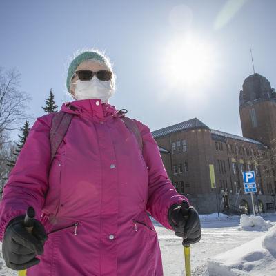 Meeri Kareinen sauvakävelyllä auringonpaisteessa Joensuun kaupungintalon edessä.