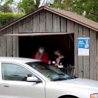 Kaksi vaalivirkailijaa on kojussa vastaanottovat autolla äänestämään tulleen henkilön.