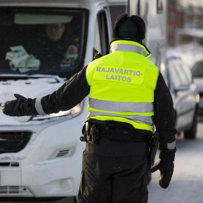 En person vid gränsbevakningen vinkar in en bil vid Torneå-gränsen.