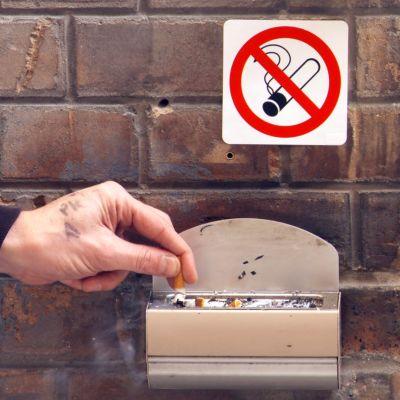 """Käsi sammuttaa savukkeen tuhkakuppiin. Yllä """"tupakointi kielletty"""" -merkki."""