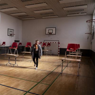 Rehtori kävelee luokkahuoneeksi muutetussa jumppasalissa.