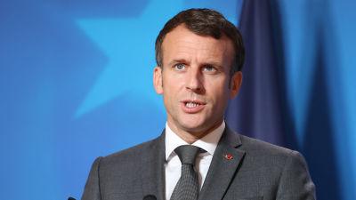 Frankrikes president Emmanuel Macron håller tal. I förgrunden syns två mikrofoner, i bakgrunden en blå bakgrundsskärm.