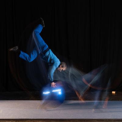 Rauli Dahlberg tekee akrobatiatemppuja fitnespallon kanssa.