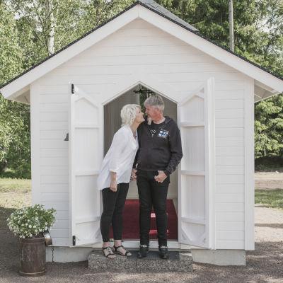 Kvinna och man står hand i hand framför en väldigt liten, vit kyrka.