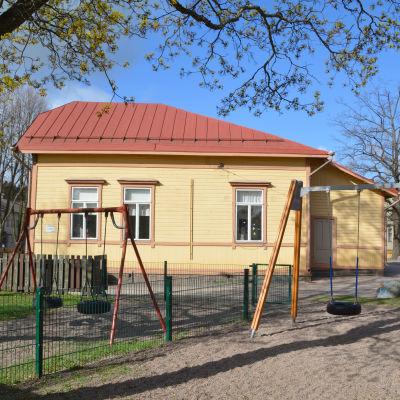 ett gult trähus och gungor
