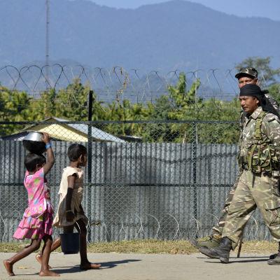 Barn och militär promenerar i den nordöstra delstaten Assam.