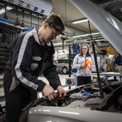 Vasemmalla automekaanikko Olli Mantela tekee töitä auton konepellin alla. Keskellä Terhi Takkinen vihko kädessään.
