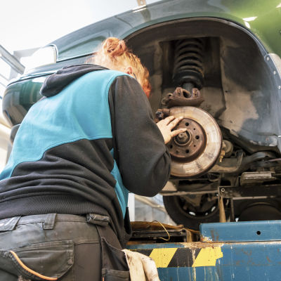Oppilas korjaa auton jarruja.