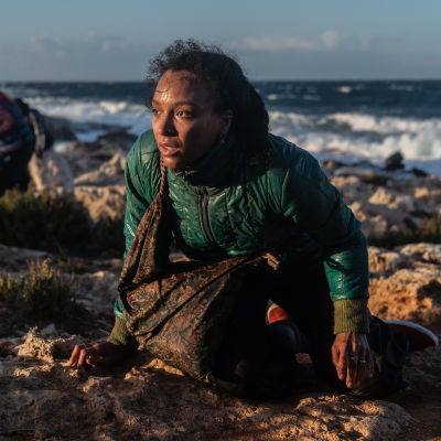 Kiki (Evelyn Rasmussen Osazuwa) istuu puoliksi meren äärellä väsyneen näköisenä.