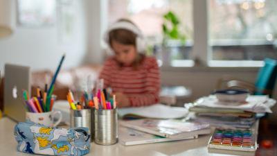 Ett barn sitter vid en dator med hörlurar på huvudet. Framför på bordet ligger skolböcker och burkar fyllda med olika sorters pennor.