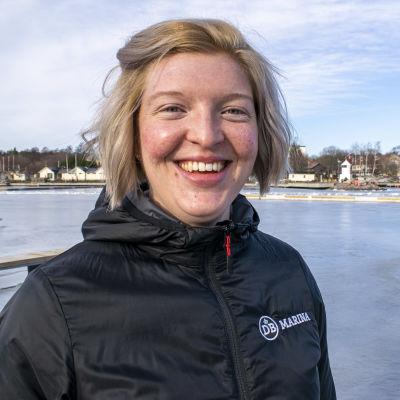 Seidi Lindroos står i svart jacka och visar upp Dalsbruks gästhamn.
