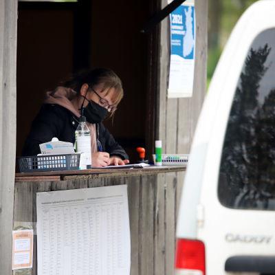 vaalivirkailija täyttää ennakkoäänestäjän papereita kojun tiskillä. Häntä vastapäätä on äänestämään tulleen auto.