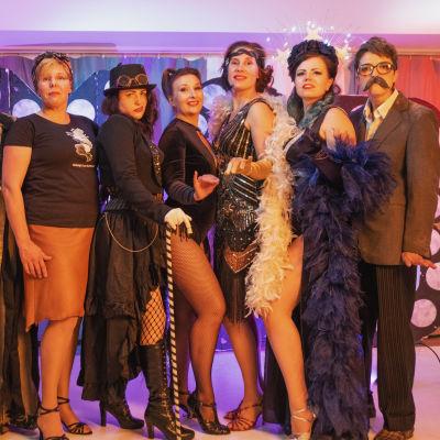 Ryhmäkuva erilaisiin esiintymisasuihin pukeutuneista burleski-harrastajista.
