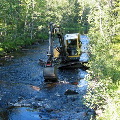 Kone siirtää kiviä joessa.