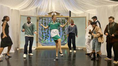 Dansande skådespelare på en scen.