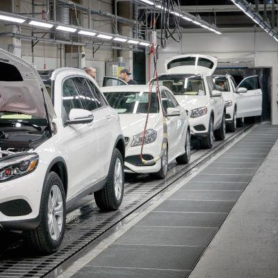 Vita bilar på en rullande band i en bilfabrik.