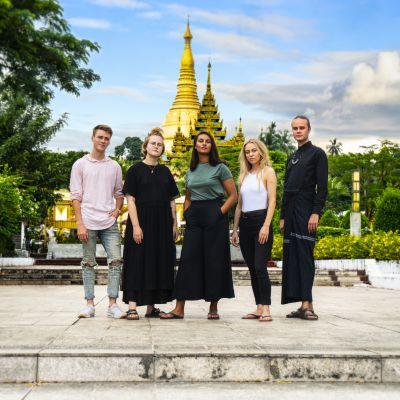 Viisi suomalaista nuorta poseeraa MyanmarinYangonissa temppelin edustalla.