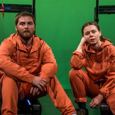 Skådespelarna Ole Øwre och Elisa Makarevitch sitter på marken iklädda orange overaller, i bakgrunden syns en grön skärm.