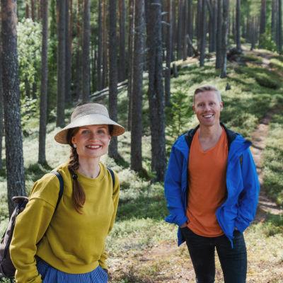 Egenlandin juontajat Hannamari Hoikkala ja Nicke Aldén seisovat metsäisellä harjulla, taustalla näkyy polku.