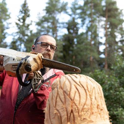 Juha Käkelä veistää moottorisahalla puista leijonaa pihalla.