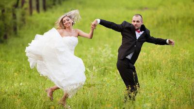 Man och kvinna i bröllopskläder hoppar upp i luften på grön äng