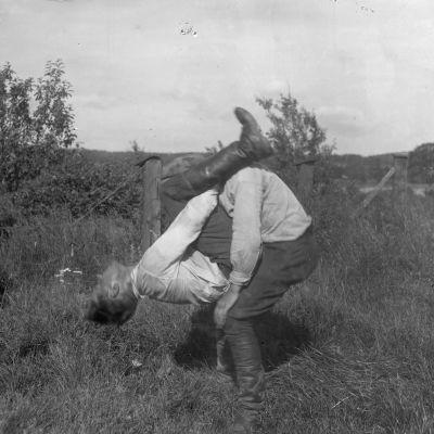 """Två män leker leken """"prova nacke"""", där den ena ska lyfta upp den andra med bara sin nackes styrka. Bilden är tagen 1930 i Bromarf."""