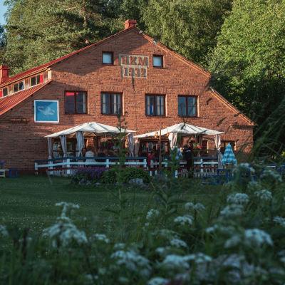 Gammal ladugård i rödtegel, framför byggnaden en terrass med vita tälttak. Gården är omgärdad av gräsmatta och i förgrunden vita blommor.