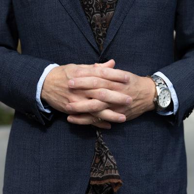 Miehen kädet ristissä vatsan päällä.