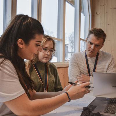 Tre unga personer, studerande, sitter vid ett bord med bärbara datorer och pennor och papper och diskuterar.