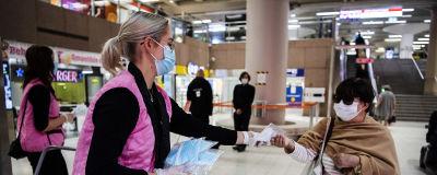 Människor som bär munskydd inomhus. Gratis munskydd delas ut vid Helsingfors järnvägsstation i augusti 2020..