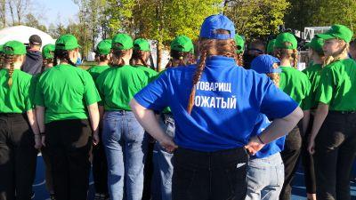 En kvinna i blå blus och keps övervakar en grupp tonårsflickor som är klädda i gröna t-tröjor och gröna kepsar. Alla står med ryggen mot kameran.