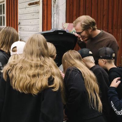 Luokanopettaja Janne Puolitaival esittelee koululaisille kompostin toimintaa.