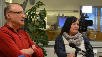 Kaj Karlstedt och Sari Wilhola. Två Ingåpolitiker sitter vid ett bord i en radiostudio. En mikrofon, papper och pennor på bordet.