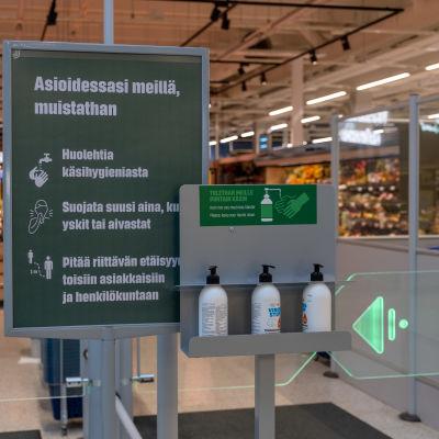 Ohjeistusta sekä käsidesipulloja S-marketin sisäänkäynnillä.