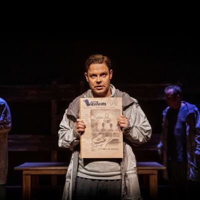 Petr Ginz (Patrick Henriksen) håller upp en tidning.