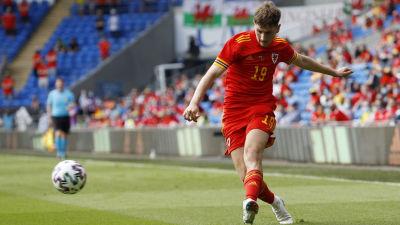 Fotbollsspelare i roströd speltröja sparkar en boll under match.