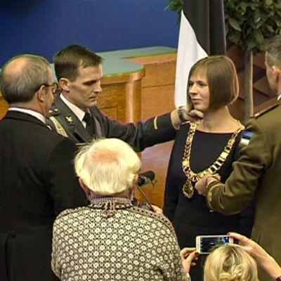 adjutantit asettavat presidentin käädyt uuden presidentin kaulaan