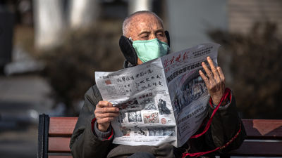 Man med andningsskydd läser tidning.