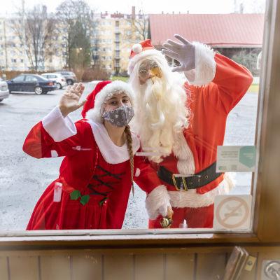 Tyttötonttu ja joulupukki vilkuttavat ulko-oven lasin takana.