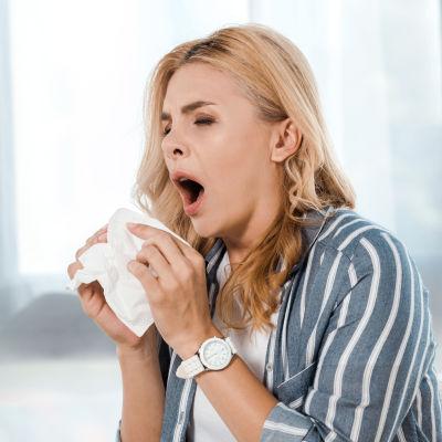 Kvinna sitter i soffa och nyser, lyfter en näsduk mot ansiktet.