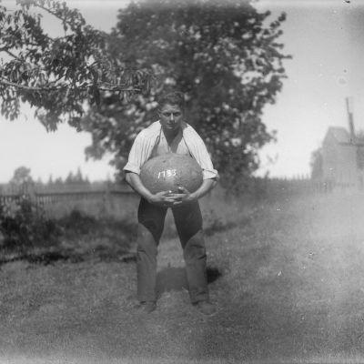 En man lyfter en stor sten med sina händer. Bilden är tagen 1930 i Jomala, Björsby, Åland.