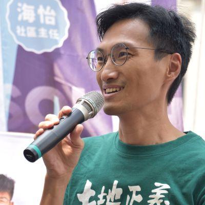 Man i grön t-skjorta talar i en mikrofon och ser glad ut.