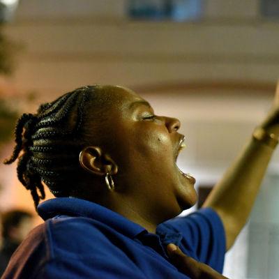 Demonstrant ropar slagord i Charlotte, North Carolina. I handen håller hon en telefon.